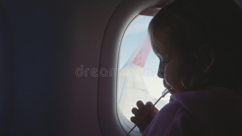 Silhouette девушка ребенка всасывая помадки на деревянной ручке над иллюминатором в самолете стоковые фото