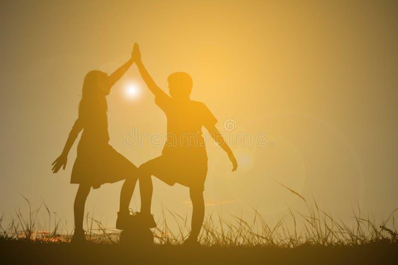 Silhouette дети играя футбол на заходе солнца неба Время дальше стоковое изображение