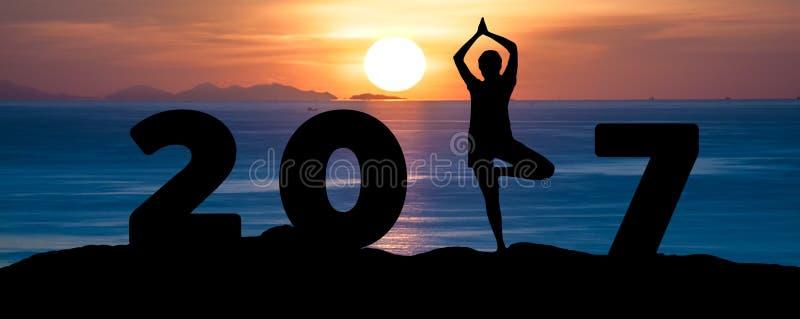 Silhouette йога игры молодой женщины на море и счастливом Новом Годе 2017 пока празднующ Новый Год стоковая фотография