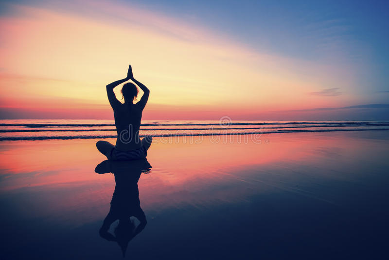 Silhouette йога молодой женщины практикуя на пляже моря на сюрреалистском заходе солнца Природа стоковые изображения