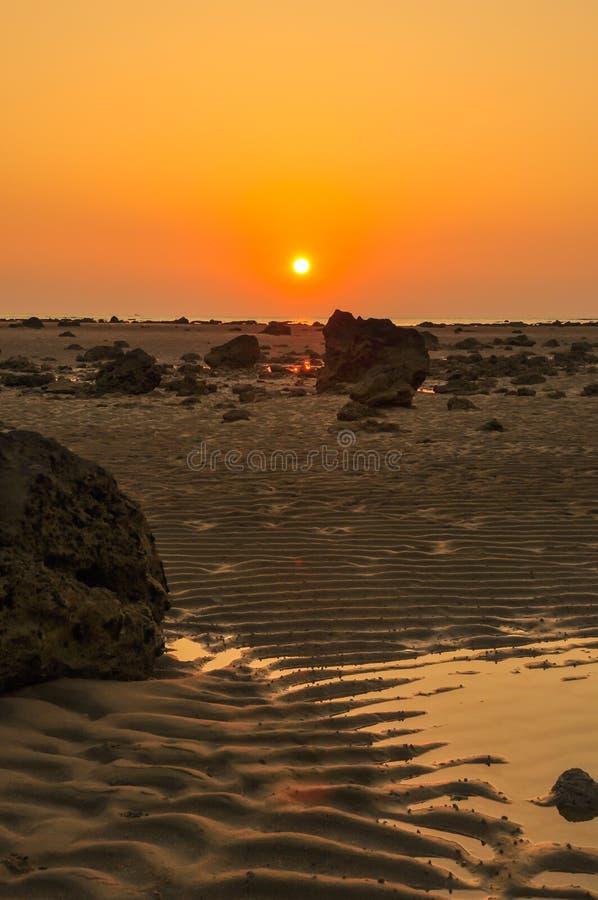 Silhouette красное небо над скалистым ландшафтом захода солнца seashore стоковые фото