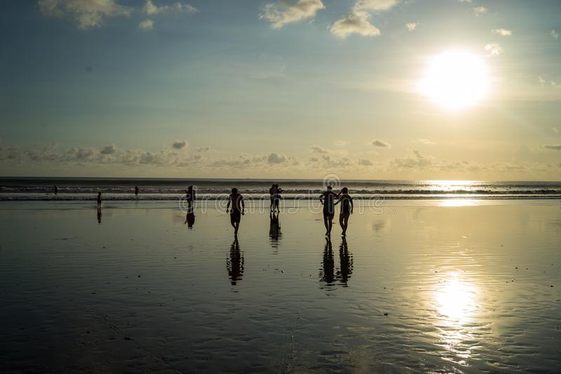 Silhouette люди во времени захода солнца на пляже Kuta, Бали-Индонезии стоковые изображения
