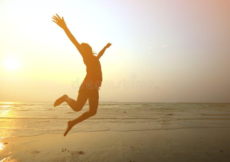 Silhouette маленькая девочка скача с руками вверх на пляже стоковая фотография rf
