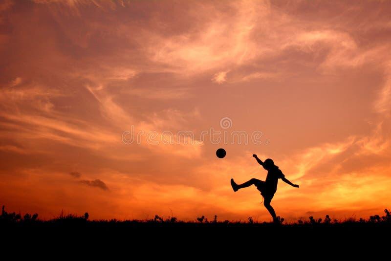 Silhouette мальчик играя футбол стоковое фото