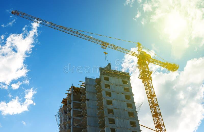 Silhouette оборудование крана конструкции, кран индустриального строительства и здание над изумительным конспектом неба захода со стоковое изображение