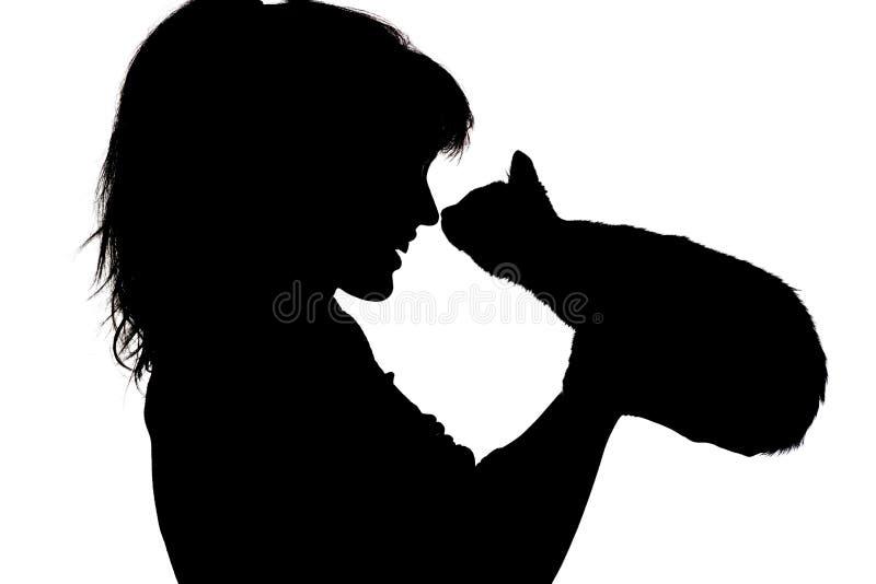 Silhouette портрет счастливой стороны которые обнюхивают для того чтобы обнюхать с малым котенком в ее оружиях, концепции девушки стоковое изображение rf
