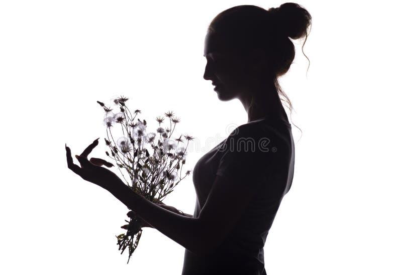 Silhouette профиль красивой девушки с букетом высушенных цветков на предпосылке изолированной белизной стоковые изображения