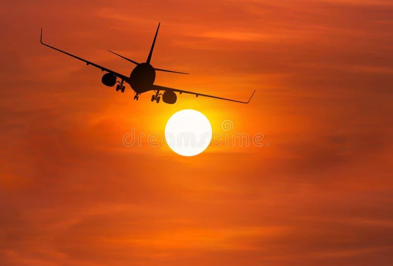 Silhouette самолет пассажира летая прочь внутри к высоченной высоте над солнцем во время времени захода солнца стоковое фото