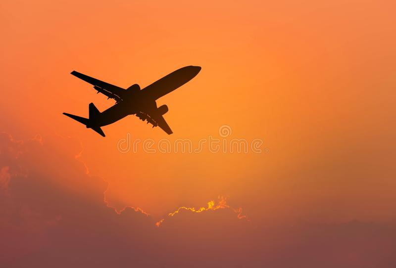 Silhouette самолет пассажира летая прочь внутри к небу во время захода солнца стоковое фото