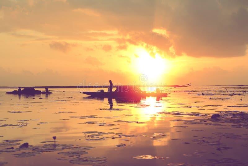 Silhouette шлюпка человека fisher в восходе солнца на озере в Таиланде стоковые фотографии rf
