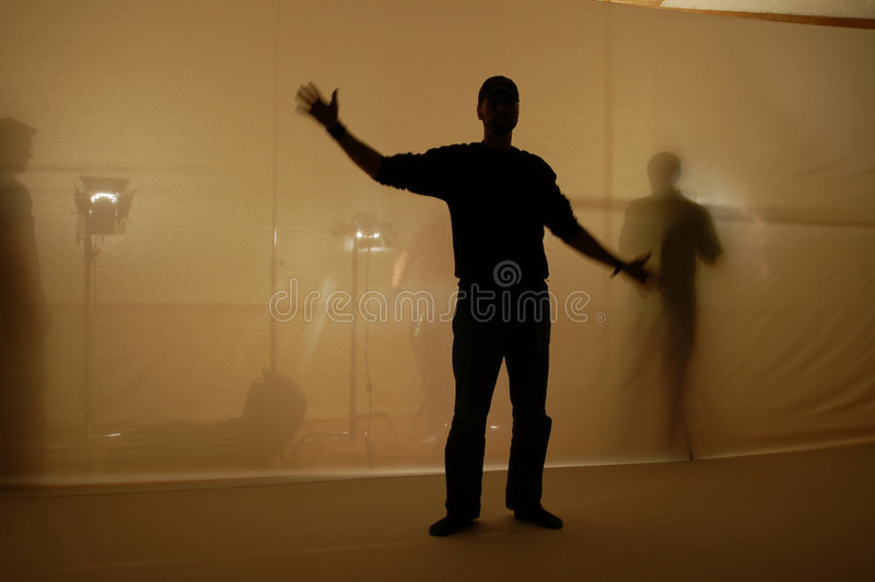 Silhouette. Actor poses for the camera on a high contrast film shoot. We see the sihouette of te actor and shadows of crew lighting equipment in the background royalty free stock image
