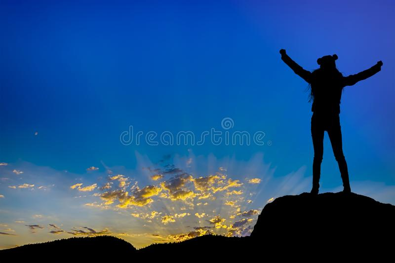 Silhouette achievements successful arm up girl is on top of hill celebrating success with sunset stock image