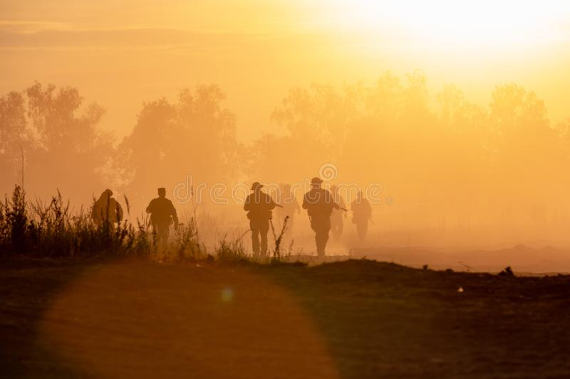 Silhouette action soldiers walking hold weapons the background is smoke and sunset. War, military and danger concept royalty free stock image