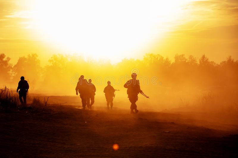 Silhouette action soldiers walking hold weapons the background is smoke and sunset and white balance ship effect dark stock image
