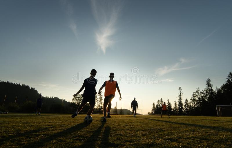 Boys playing soccer at sunset. Silhouette action sport outdoors of a group of kids having fun playing soccer football royalty free stock photos