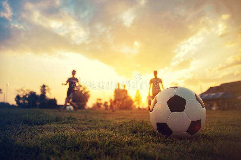 Silhouette action sport outdoors of a group of kids having fun playing soccer football for exercise in community rural area under stock image
