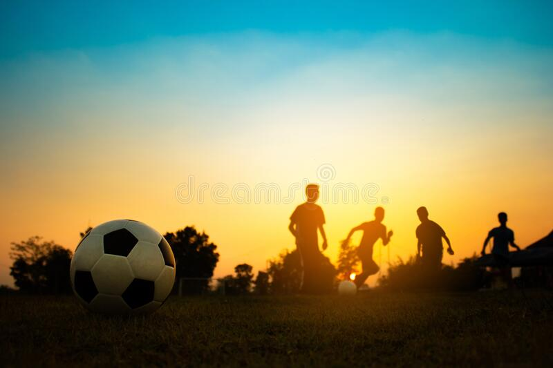 Silhouette action sport outdoors of a group of kids having fun playing soccer football for exercise in community under royalty free stock photo