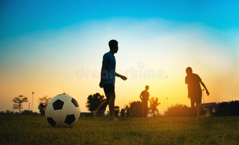 Silhouette action sport outdoors of a group of kids having fun playing soccer football for exercise in community under stock image