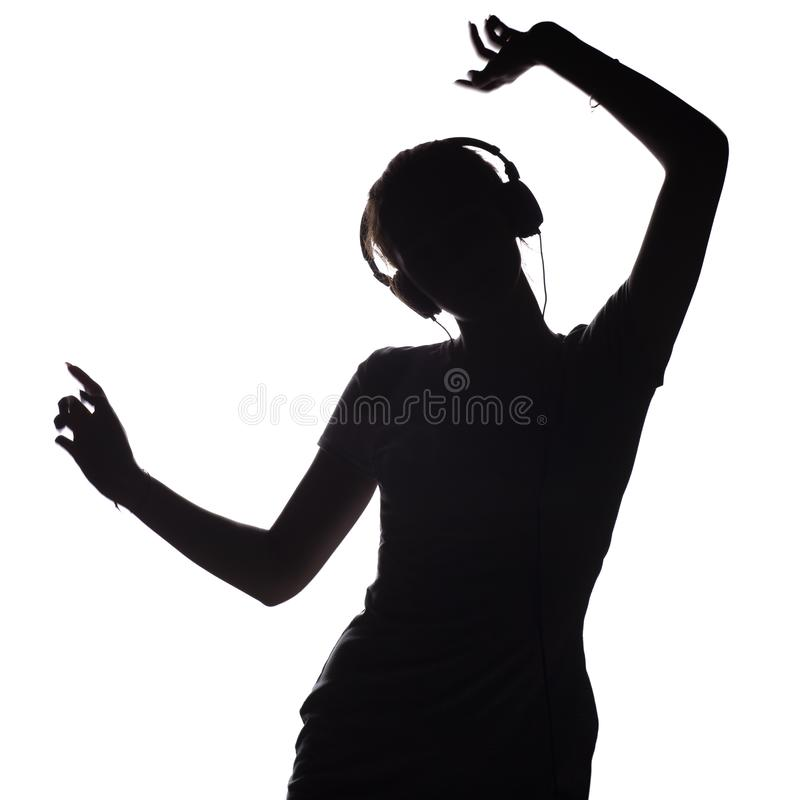 Silhouette of a active girl listening to music in headphones, figure of young woman dancing with hands up on a white isolated royalty free stock image