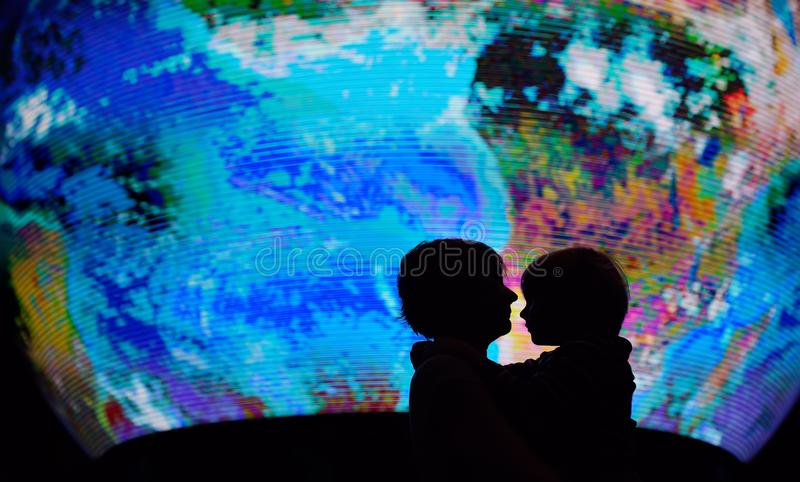Silhouette of adult and child on background of globe earth. Ecologic and protection environment concept stock photo
