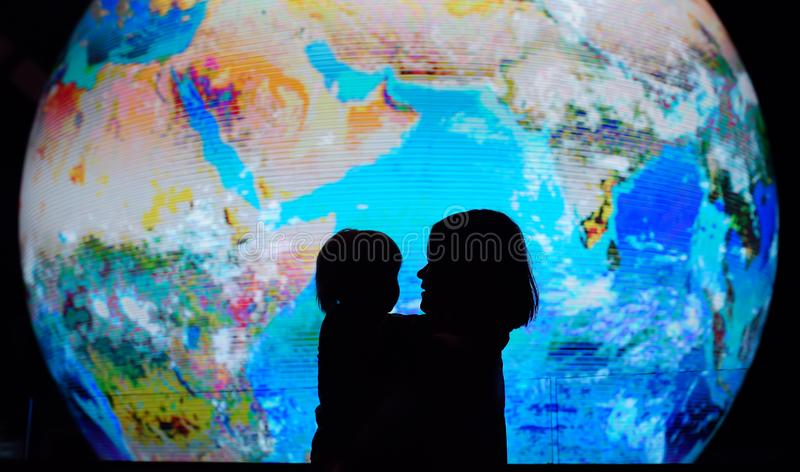 Silhouette of adult and child on background of globe earth. Ecologic and protection environment concept royalty free stock photo