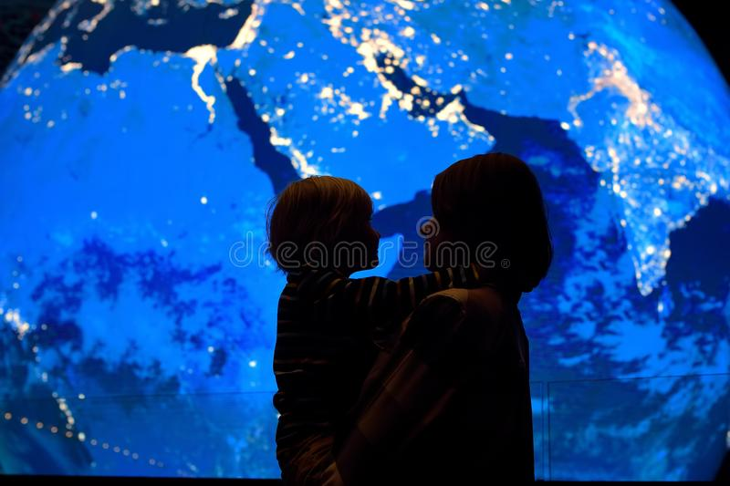 Silhouette of adult and child on background of globe earth. Ecologic and protection environment concept stock images