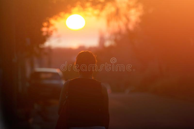 Silhouette of adult woman walking alone along city street during beautiful warm sunset stock images