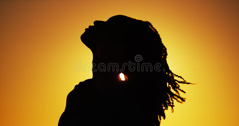 Silhouette of African woman standing at sunset royalty free stock photography