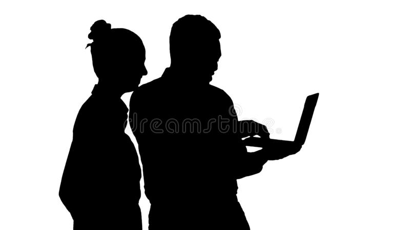 Silhouette Afro american business adviser showing something on laptop screen talking to white businesswoman. stock photo