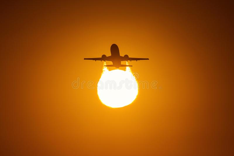 Silhouette of an air plane over the sun with beautiful red clouds in background.  royalty free stock photography