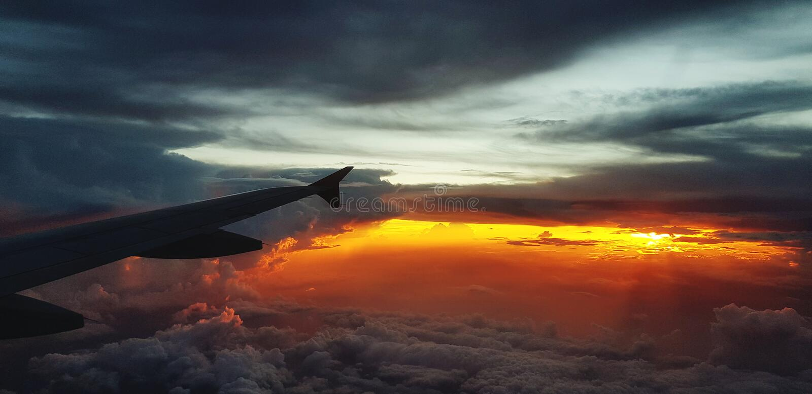 Silhouette of aircraft or airplane wing on dark sky with sunset light background royalty free stock photography