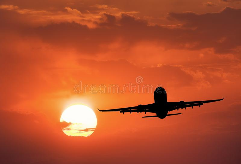 Silhouette of the aircraft and red sky with sun. Landscape with passenger airplane is flying in the sky with clouds at sunset. Travel background. Passenger stock photography