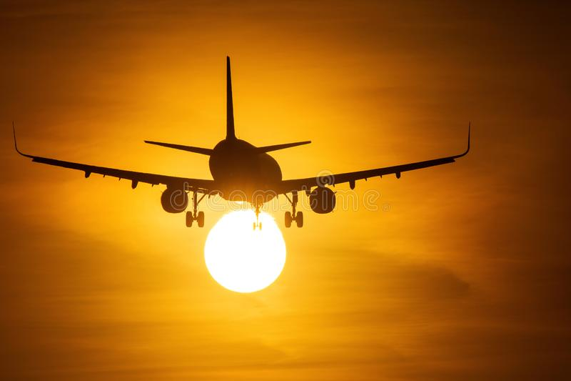 Silhouette of airplane flying at sunset over the sun with beautiful clouds in background stock photography
