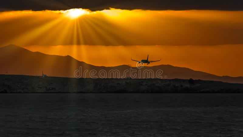 Silhouette of Airplane over Body of Water stock photography