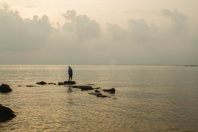 Silhouette alone fisherman stands on rock at sea shore for fish hunt royalty free stock photography