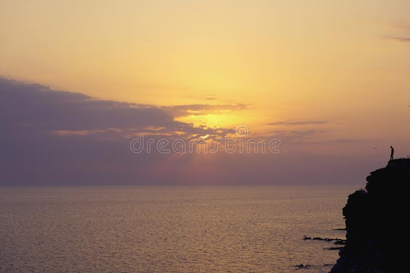 Silhouette alone lonely man are standing on hill against sunset purple orange sky with round sun over sea stock photo