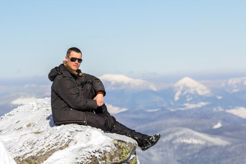 Silhouette of alone tourist sitting on snowy mountain top enjoying view and achievement on bright sunny winter day. Adventure, royalty free stock image