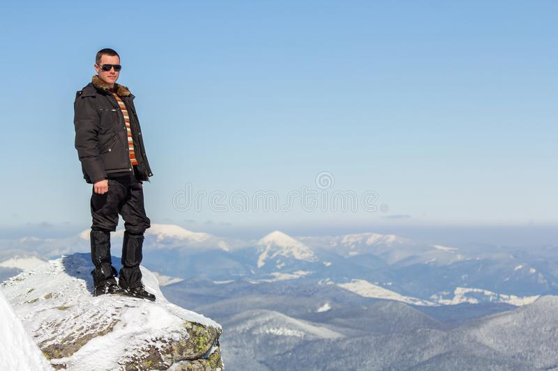 Silhouette of alone tourist standing on snowy mountain top enjoying view and achievement on bright sunny winter day. Adventure, royalty free stock photo