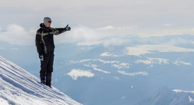 Silhouette of alone tourist standing on snowy mountain top in winner pose with raised hands enjoying view and achievement on royalty free stock images