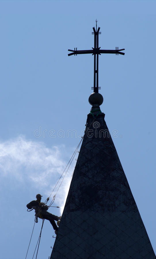 Silhouette Of The Alpinist Cleans Church Roof Royalty Free Stock Image