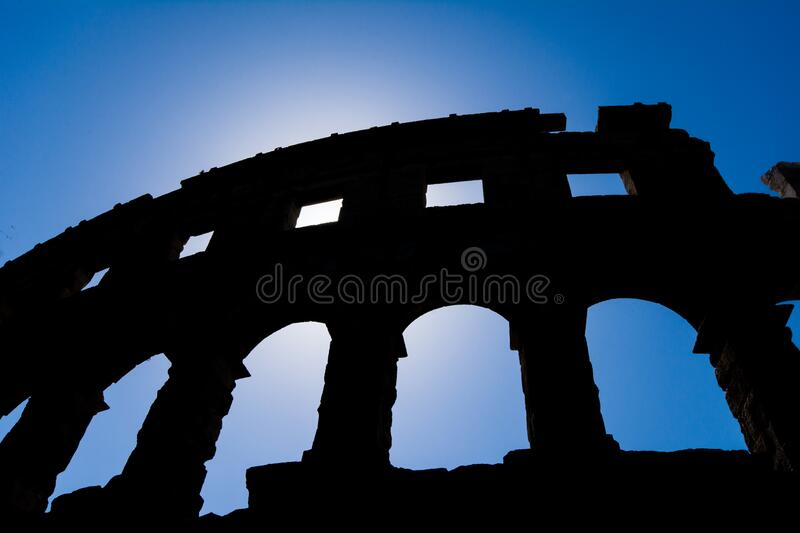 Silhouette of the ancient amphitheater in pula croatia. With blue sky royalty free stock photo