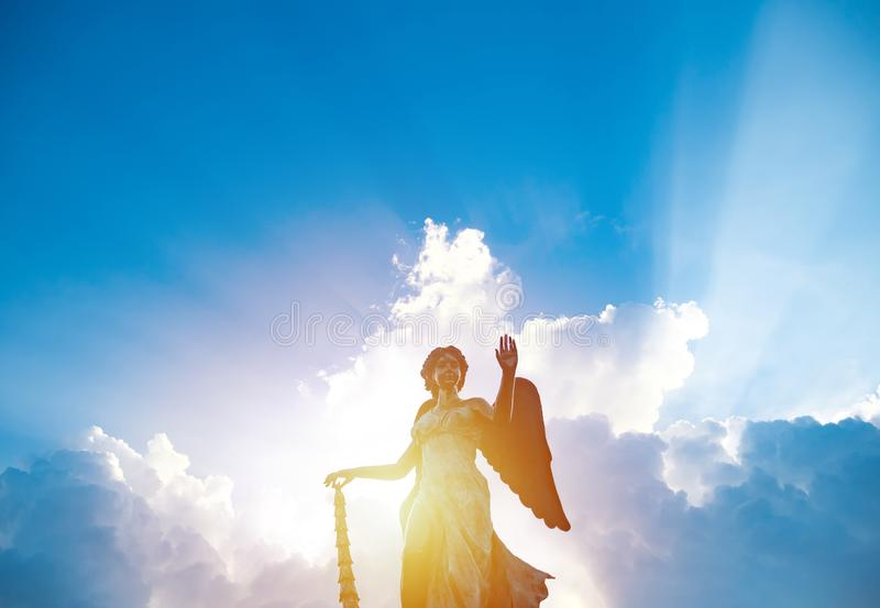 Silhouette of angel statue sculpture with sunlight shining behind white cloud with blue sky background. stock photos