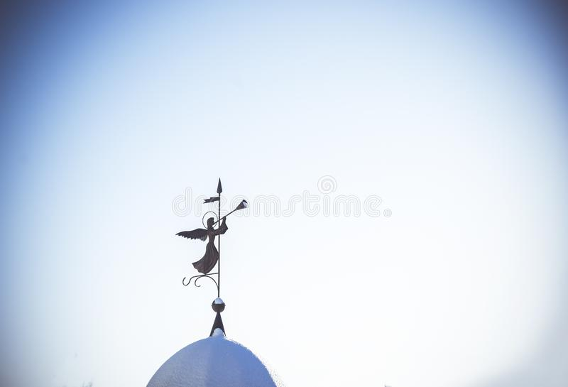 Silhouette of an angel. Weathervane on the dome of the temple against clean blue sky. The concept of peace and religion stock photos