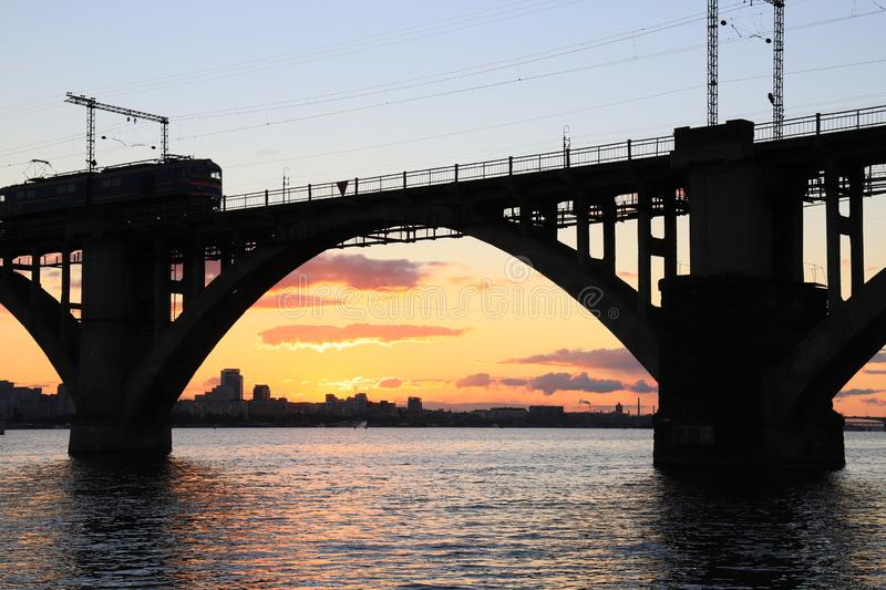 Silhouette of arched railway bridge and a train  at beautiful sunset. Dnieper river, Dnipo city,  Ukraine. Silhouette of arched railway bridge and a train  at royalty free stock photo