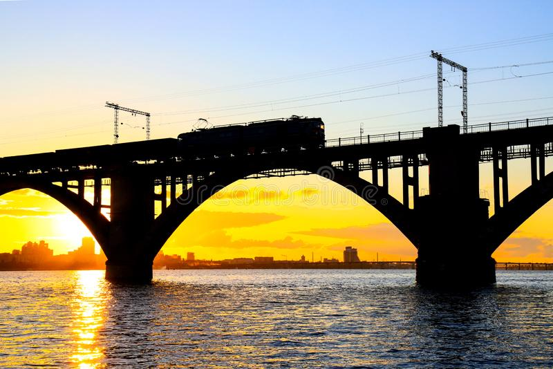 Silhouette of arched railway bridge and a train on the Dnieper river at beautiful sunset. Dnipo city, Dnepropetrovsk. Ukraine royalty free stock photography