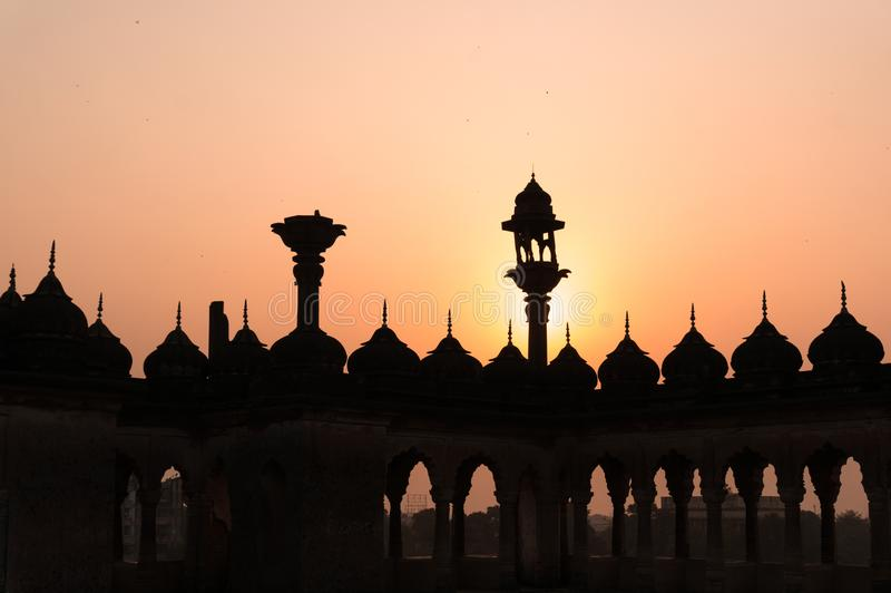 Silhouette of arches and lamps in mughal architecture. Silhouette of arches and lamps on the roof of the bara imambara complex in lucknow. Beautiful details of royalty free stock photos