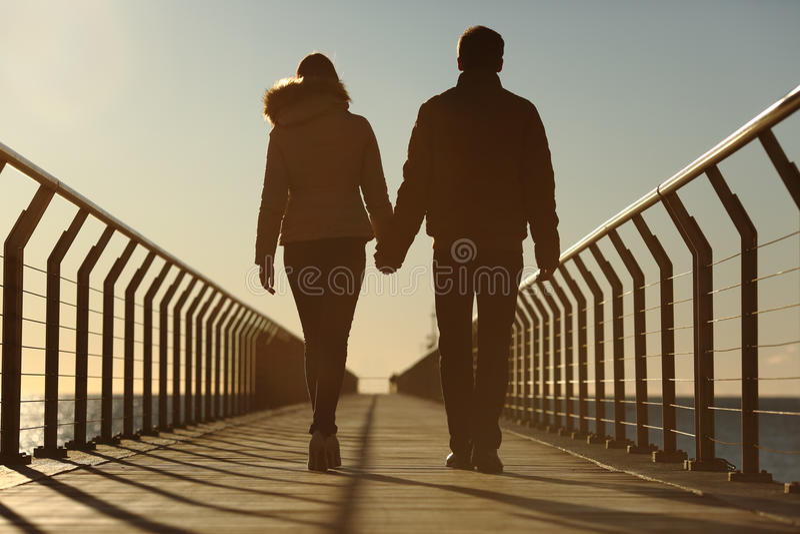 Silhouette arrière d'un couple marchant tenant des mains photo stock
