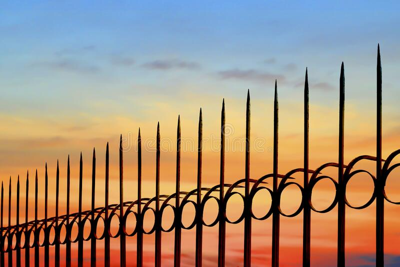 Silhouette arrow spiky metal fence against sunset sky background. Silhouette arrow spiky metal fence against colorful sunset sky background, side view with copy royalty free stock images