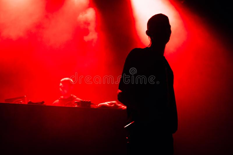 Singer and artist on the stage in red light. stock photos