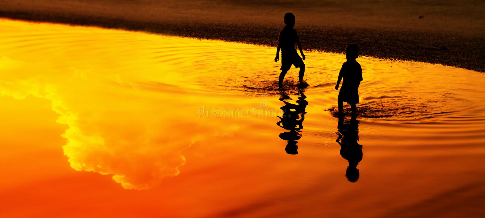 Silhouette of 2 Asian boys on  the beach. Silhouette of 2 Asian boys on  the beach in the sunset royalty free stock images